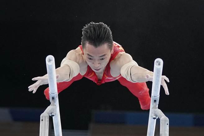 東京奧運體操項目3日下午最後一天賽程,中國體操隊選手鄒敬園在男子雙槓比賽而負傷參賽,以16.233分,拿下金牌。(新華社)