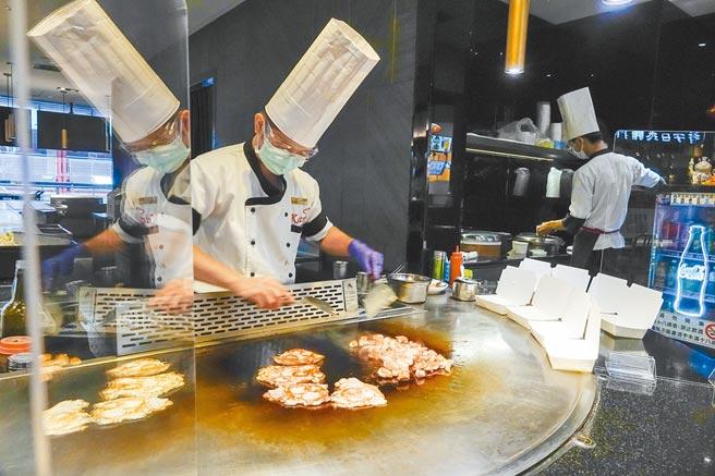 雙北、宜蘭宣布今起開放餐廳內用,圖為台北一家鐵板燒店長正在烹調客人預訂的便當,座位區已架設透明壓克力板,準備迎接客人內用。(黃子明攝)