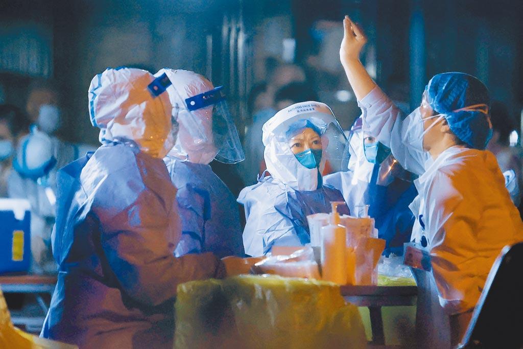 大陸本土病例持續多點擴散,上海浦東機場貨運區新增一名外航貨機服務人員確診,目前感染源不明。圖為醫護人員正在進行核酸採樣前準備工作。(中新社)