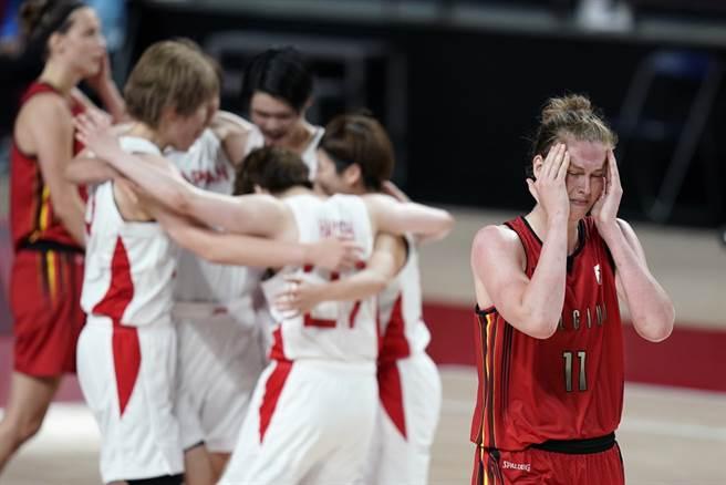 比利時中鋒梅瑟曼掩面痛哭,跟後方日本球員慶祝勝利畫面形成強烈對比。(美聯社)
