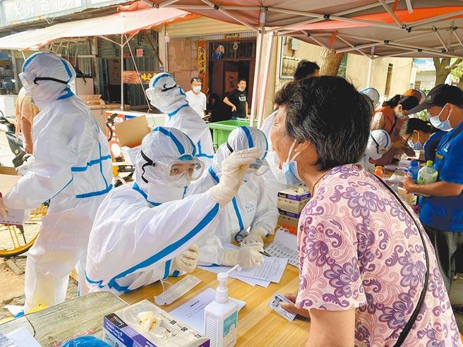 湖北武漢再現本土病例,全市進行核酸檢測,圖為武漢大學人民醫院醫護人員為經開區居民進行核酸採樣。(中新社)