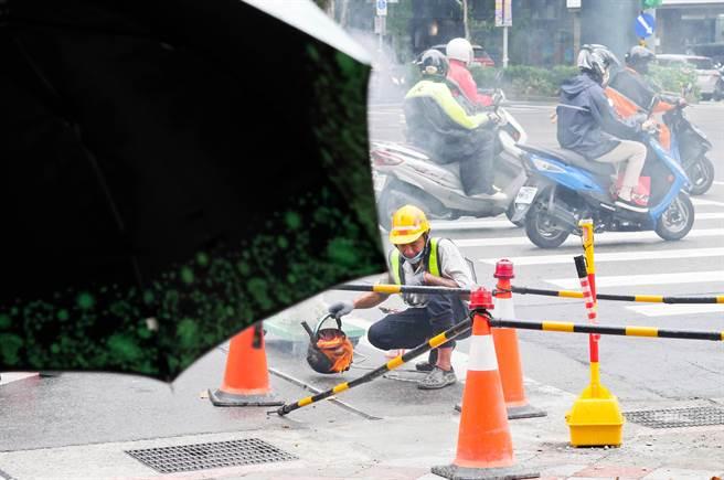 疫情逐漸趨緩,全國防疫警戒已降至二級,行政院規畫將推出「振興五倍券」。圖為今日台北市街頭一位勞工在下著小雨的馬路邊,辛苦燒著柏油準備填好縫隙。(陳俊吉攝)