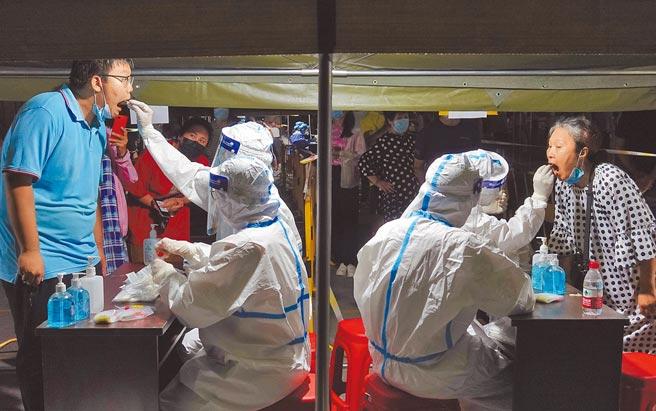 大陸本土疫情呈現多點爆發,山東煙台啟動主城區全員核酸檢測,醫務人員為市民進行核酸檢測取樣。(新華社)