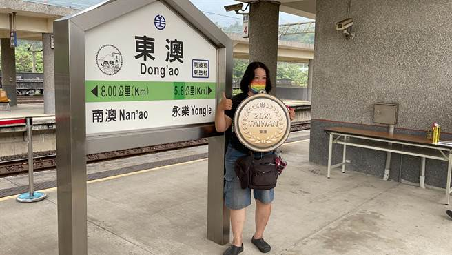 民眾捧著台鐵特製的「東澳金牌」,與東澳站的站牌一起合影留念。(讀者提供/胡健森宜蘭傳真)
