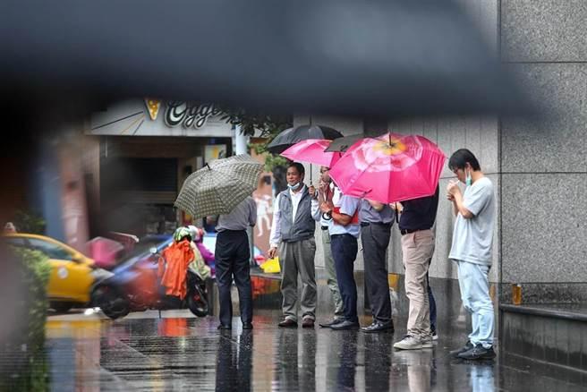 受到盧碧颱風外圍環流影響,中央氣象局針對中南部10縣市發布豪雨、大雨特報,未來幾天雨勢不能輕忽。6日北部地區飄著間歇性的雨勢,民眾撐傘聚在外頭抽煙,形成一幅奇特的景象。(未成年請勿抽煙)(鄧博仁攝)