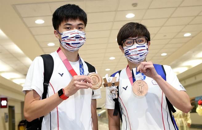 東奧中華台北桌球及拳擊選手6日返台,奪下桌球混雙銅牌的林昀儒(左起)及鄭怡靜下機後開心地展示獎牌。(范揚光攝)
