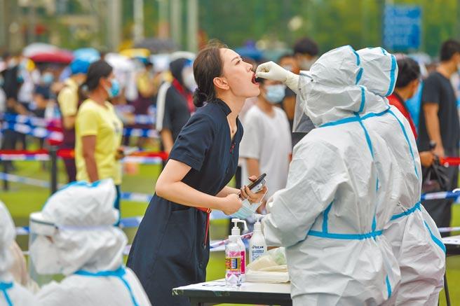 大陸繼南京和上海的機場成為疫情破口後,海南省海口美蘭機場也出現1名人員確診。圖為5日美蘭機場工作人員排隊接受核酸檢測。(中新社)