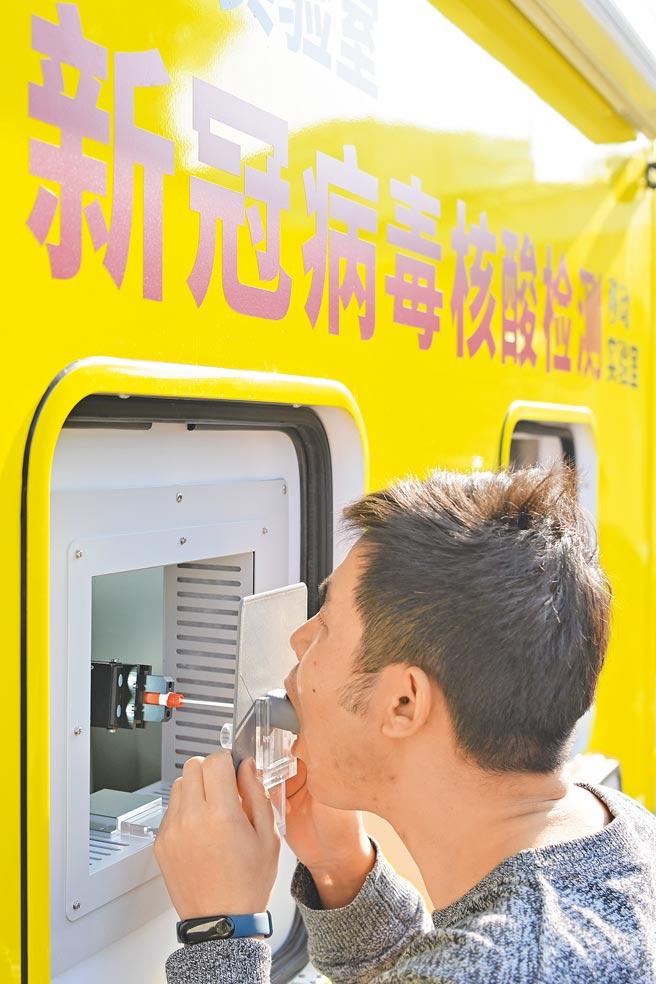 大陸湖北出動首輛移動核酸檢測車支援全民檢測。圖為日前廣東省廣州市核酸自動檢測車,車內的口腔咽拭子採樣機器人自動採樣。(中新社)