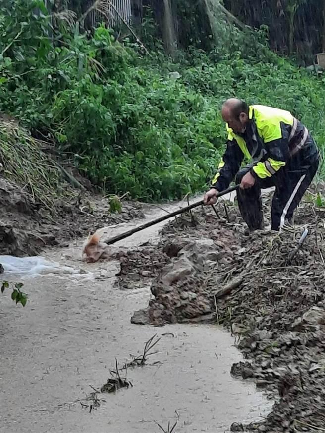 大湖警分局校林派出所所長胡育良冒雨協助居民開挖水道排水。(大湖警分局提供/謝明俊苗栗傳真)