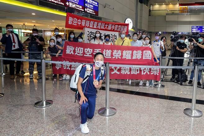 小清新」文姿云(前)在東京奧運空手道女子55公斤量級拿下銅牌,空手道為此次東京奧運選辦項目,首度在奧運舞台亮相。空手道隊於8日傍晚返台,文姿云的父親(後方黃衣者)也到機場接機,但因為防疫的關係,只能遠遠合照。(陳麒全攝)