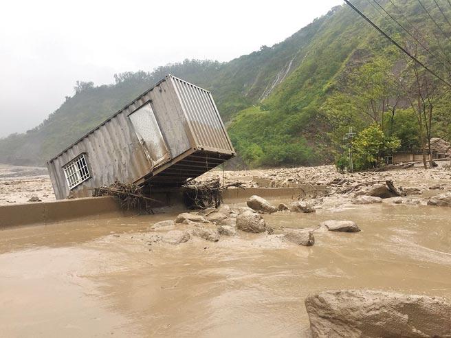 高雄市有貨櫃屋被土石流沖至荖濃溪和玉穗溪交界處,騰空懸在石塊上。(讀者提供/石秀華高雄傳真)