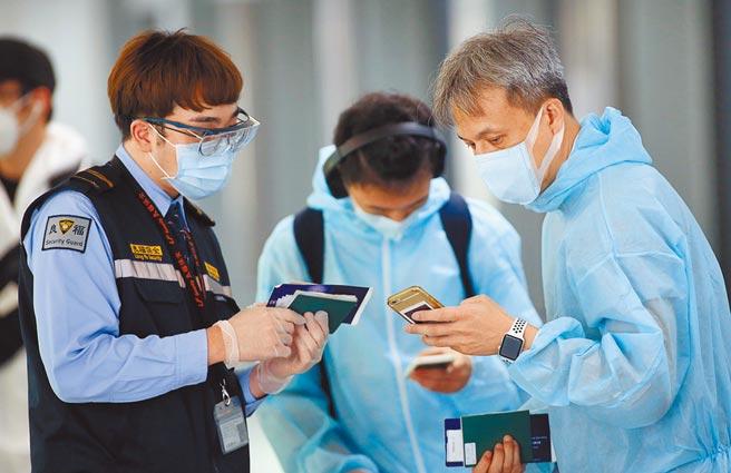 中央流行疫情指揮中心7日公布,國內新增10例新冠肺炎確定病例,其中4例為境外移入,在桃園機場第二航廈的入境管制區,剛下機的旅客正在查驗入境健康資料。(范揚光攝)