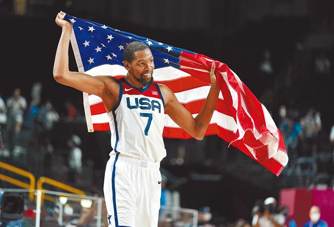 杜蘭特高舉美國國旗慶祝奪金。美國男籃在金牌戰以87比82險勝法國,完成4連霸。(美聯社)