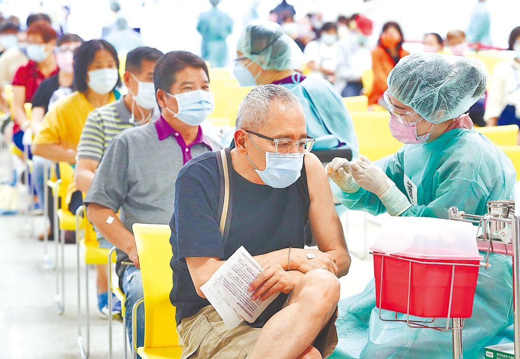 台北市花博爭豔館接種站9日施打疫苗,醫護幫現場民眾施打第1劑AZ疫苗。(陳俊吉攝)
