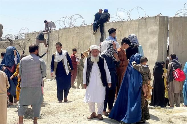 塔利班奪回阿富汗,大批阿富汗民眾倉皇逃難,甚至試圖爬牆闖入喀布爾機場。(圖/路透社)