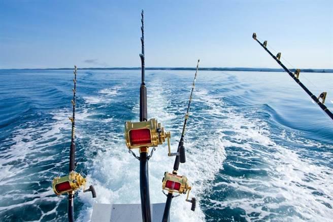 3名男子合力釣到「海中巨無霸」,卻遲遲無法將大魚拉上船,反倒是手上的釣魚竿讓網友全歪樓。(示意圖/達志影像)