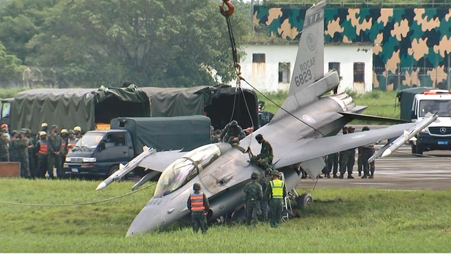 空軍F16昨日在屏東屏北機場漢光預演時,竟滑出跑道導致機頭插入土裡,目擊者指出,戰機快到終點時有丟阻力傘但煞不住,最後「吃土」。(民眾提供/謝佳潾屏東傳真)