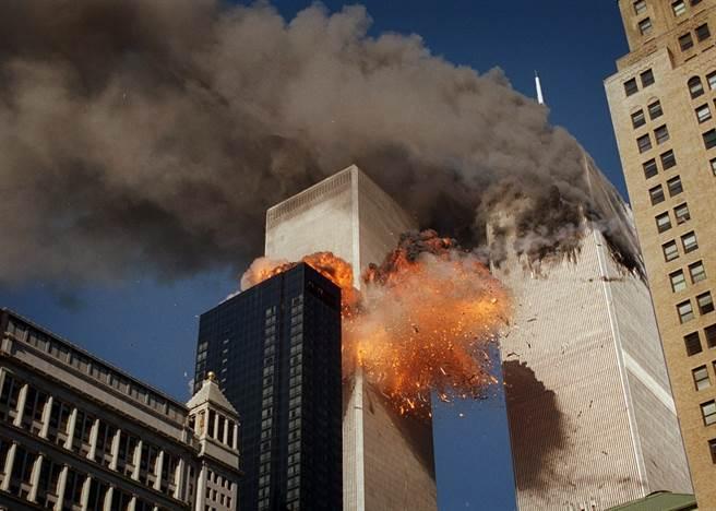 飛機撞上雙子星大樓後,火焰及殘骸從第二棟大樓炸開,大樓冒出濃煙。(圖/美聯社)