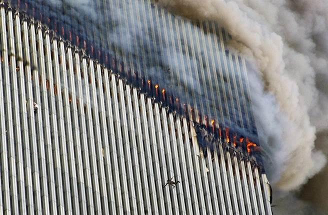 火焰及濃煙不斷從雙子星大樓北塔竄出,有一個人從高樓中摔下來,畫面左邊有另一個人緊緊攀著大樓外牆。(圖/美聯社)