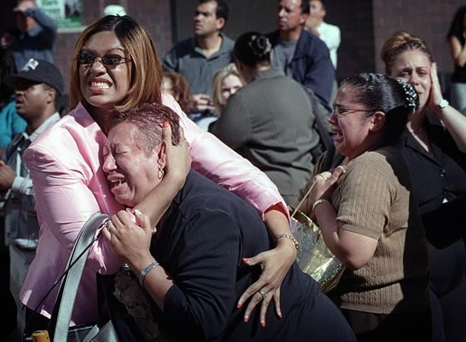 親眼看著雙子星大樓被撞、燒毀,紐約民眾抱頭痛哭,不敢置信。(圖/美聯社)