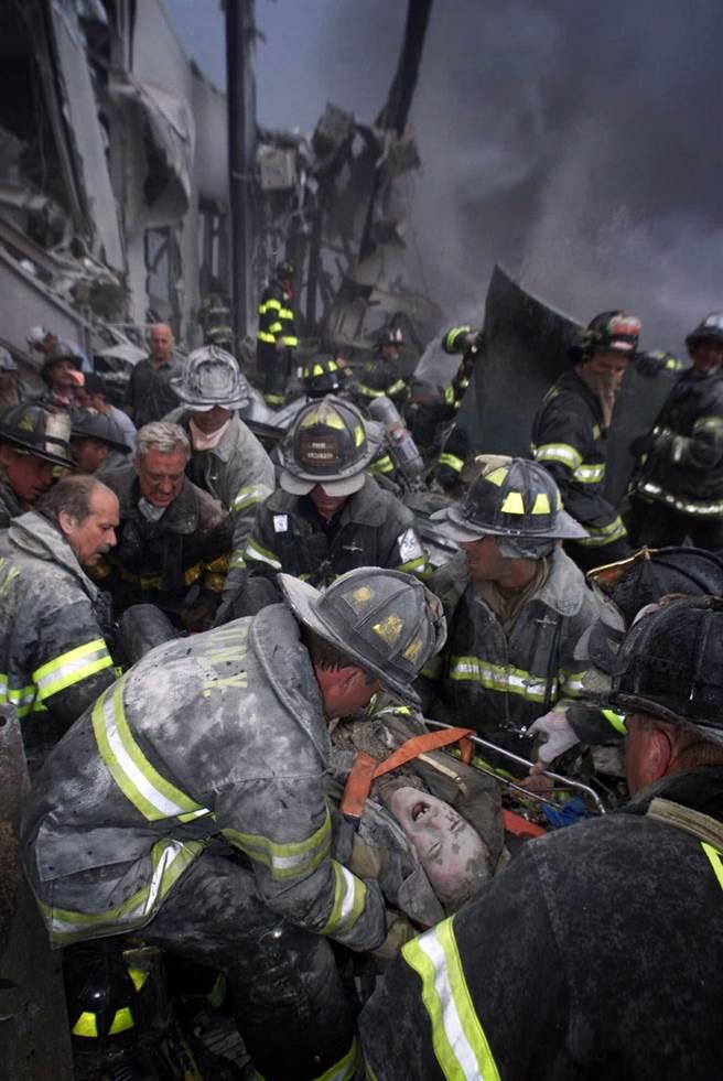 雙子星大樓倒塌後不久,一名消防員被救出,因為傷口太痛了,他忍不住尖叫。(圖/美聯社)