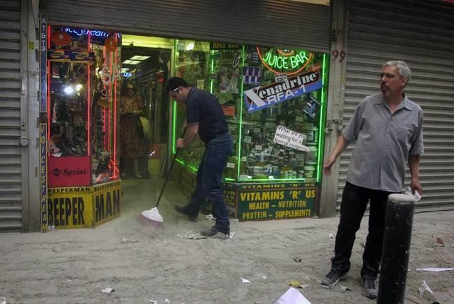 雙子星大樓倒塌後,附近街道滿布濃煙灰燼,店家忙著打掃,之後就被撤離了。(圖/美聯社)