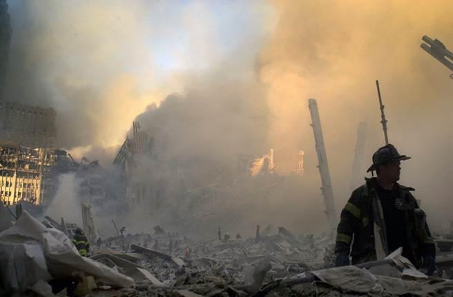消防隊員在倒塌的雙子星大樓廢墟中穿梭。(圖/美聯社)