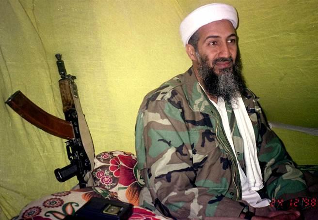 911恐攻事件幕後主使賓拉登與一小群記者會面時的畫面,身後還放著一把AF47步槍。(圖/美聯社)