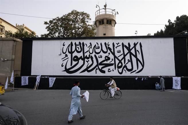 塔利班成立的「阿富汗伊斯蘭酋長國」國旗,白底上面寫清真詞,與沙烏地阿拉伯的國旗很相似。(圖/美聯社)