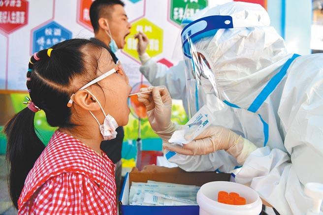 福建疫情延燒,截至13日20時,疫情熱區莆田市累計報告新冠病毒核酸陽性79例,其中確診病例58例。大陸國家衛健委專家直言,疫情存在外溢風險。圖為醫療人員為民眾採樣。(中新社)