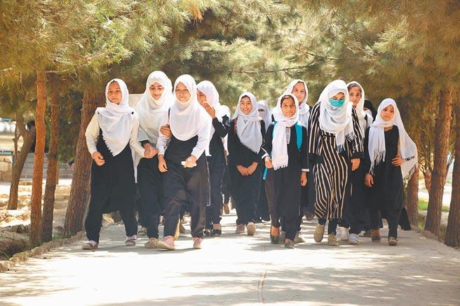 儘管塔利班承諾會按伊斯蘭教法,允許婦女受教育和工作,但塔利班高層人士稱,不應允許女性和男性一起工作。圖為阿富汗昆都士,一群女學生正前往教室上課。(新華社)