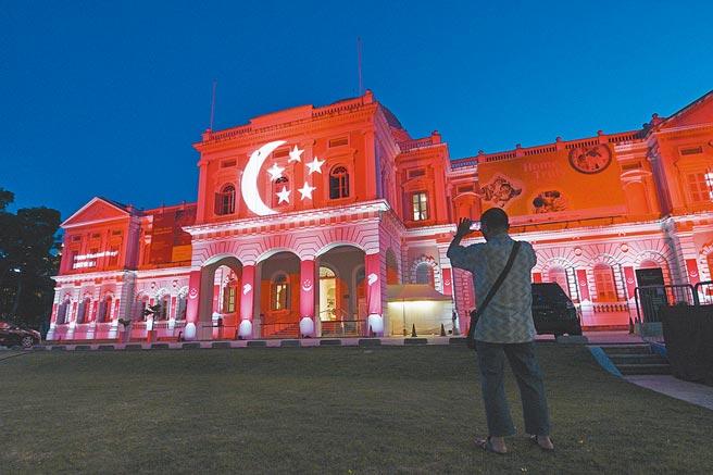 上個月(8月)10日,新加坡市區建築亮起紅色投影慶祝國慶。新加坡政府為防止外國勢力干預新加坡內政,將授權該國內政部指示社交媒體或網站經營者協助當局進行相關調查。(新華社資料照片)
