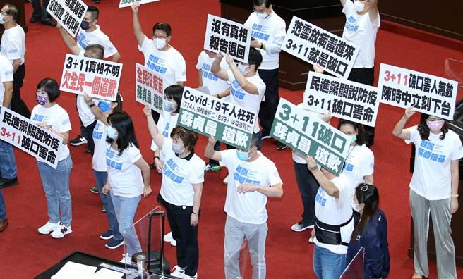 行政院長蘇貞昌17日前往立法院專案報告國籍航空機組員隔離「3+11」決策過程,國民黨立委在議場內高舉標語,要求蘇對「3+11」真相不明向全民道歉。(姚志平攝)