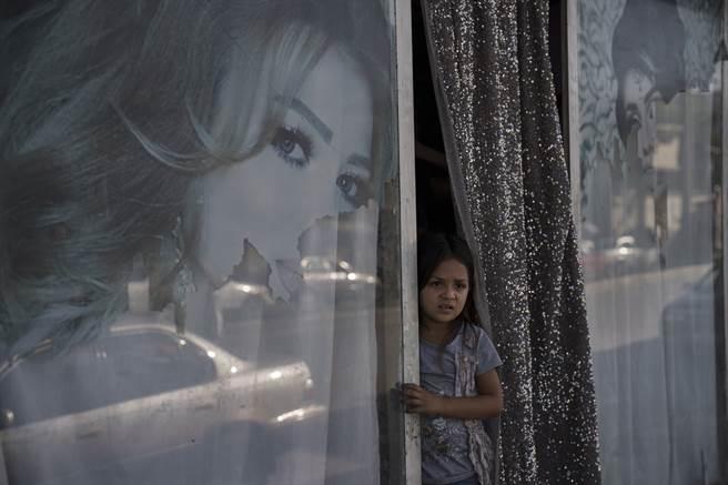 前阿富汗女市長強調,在塔利班證明將確實尊重人權之前,國際社會應停止與該組織的所有接觸。圖為一名小女孩自喀布爾美容院向外看。(圖/美聯社)