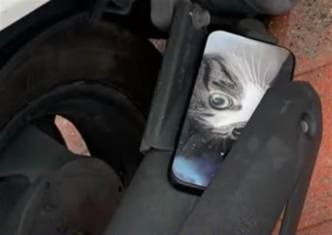 女子到派出所請警員協尋遺失的iphone手機,結果發現手機從她口袋裡滑出來,卡在機車的排氣管上。(圖/翻攝自中天電視畫面)