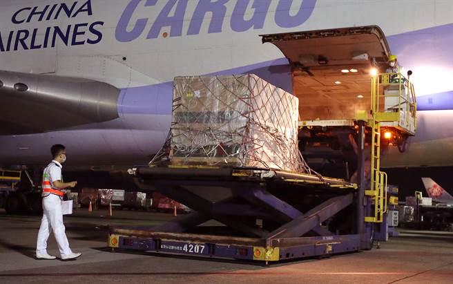 我方自購的第7批莫德納疫苗108萬劑,17日晚間由華航貨機運抵桃園機場,裝載疫苗的貨盤卸下後,一旁的海關人員立即上前核對貨物內容。(范揚光攝)