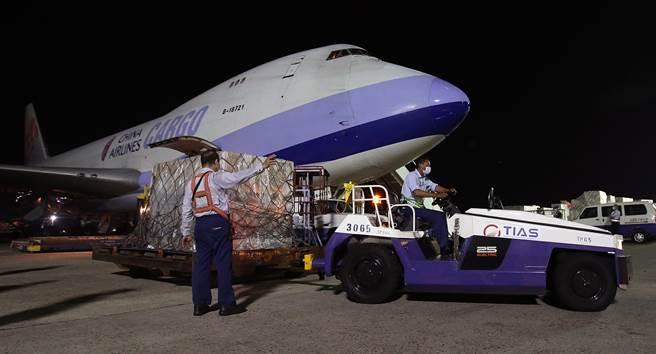 我方自購的第7批莫德納疫苗108萬劑,17日晚間由華航貨機運抵桃園機場,地勤人員卸下裝載疫苗的貨盤後,立即拖往華儲倉庫。(范揚光攝)