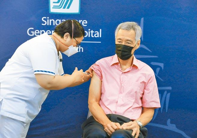 國際防疫已進入疫苗接種第3劑新階段,圖為新加坡總理李顯龍17日在中央醫院接種第3劑新冠疫苗。(路透)