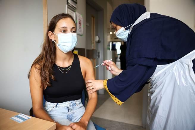 在英國一位女性正在接種輝瑞/BNT疫苗。(非本文當事人)。(圖/路透)