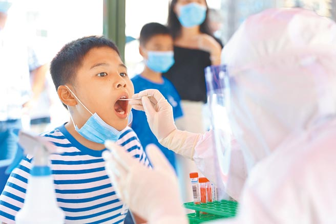 大陸福建省連日新增新冠疫情本土病例,其中不乏12歲以下學童。圖為廈門一學童正在接受核酸檢測。(新華社)