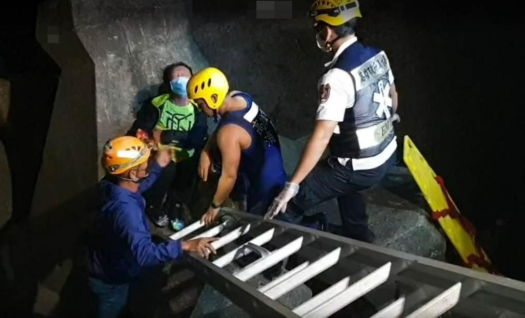 60多歲曾姓男子(左二)直接跌落在4公尺深的消波塊上,經救難人員固定確保後成功救援上岸。(民眾提供/袁庭堯高雄傳真)