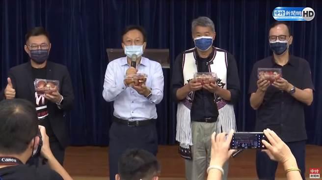 國民黨主席選舉,今日舉辦桃竹苗區政見說明會。圖為卓伯源(左二)分送蓮霧給其他候選人。(圖/中時新聞網直播畫面)