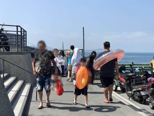 3位民眾從海興游泳池入口處走向停車場,但皆未配戴口罩。(陳彩玲攝)