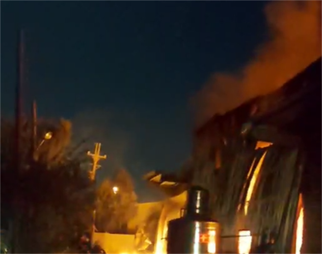 新北市林口區粉寮路二段一處鐵皮工廠21日晚間發生火災,熊熊烈火燒紅夜空。(民眾提供)