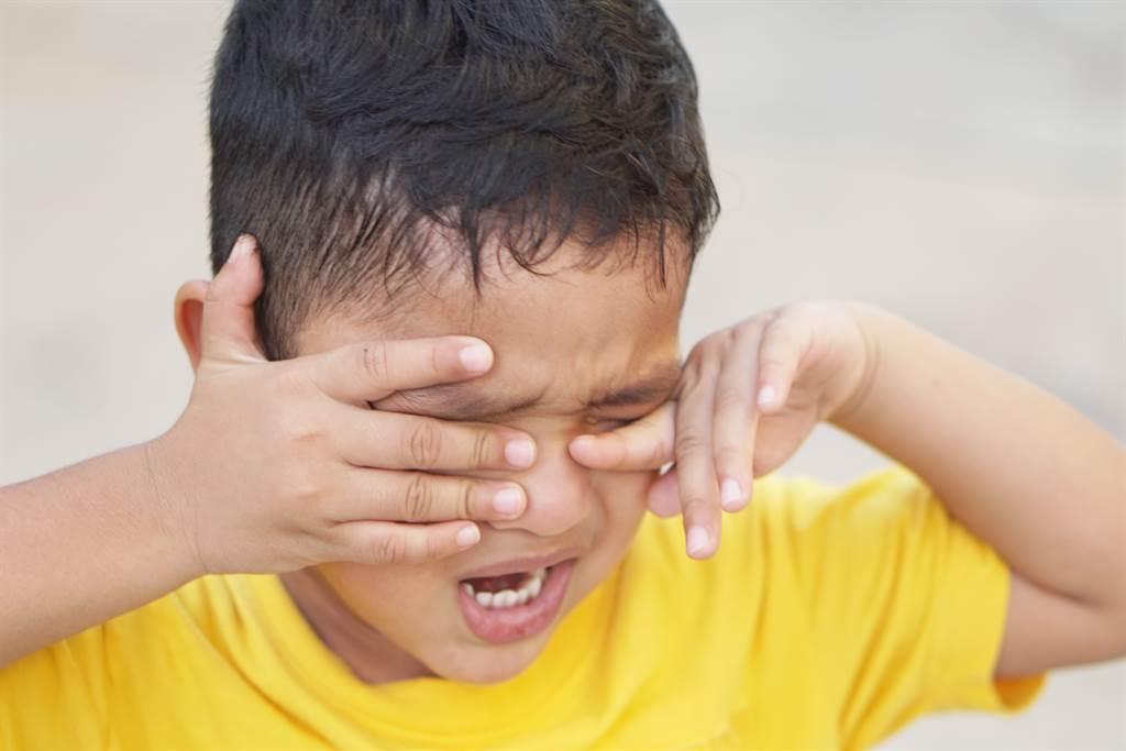 上海一位8歲男童,在客廳吃零食配卡通卻發生悲劇,手摀著眼睛在地上痛得翻滾。緊急送醫後,醫師宣布男童右眼已遭腐蝕溶解,終生失明。(示意圖/Shutterstock)