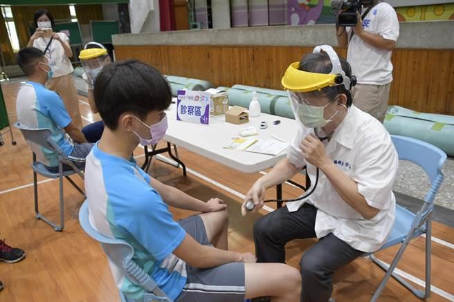 學生井然有序的進入活動中心,醫護人員將每瓶BNT疫苗分抽成6支針劑,依序幫學生注射疫苗。(吳建輝攝)
