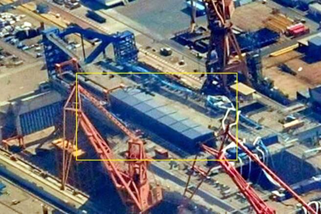 上海江南長興造船廠建造的大陸003型國產航母航拍圖顯示,甲板上彈射器位置已搭建工棚,顯示正在安裝前甲板的第2部電磁彈射器。(圖/網路)