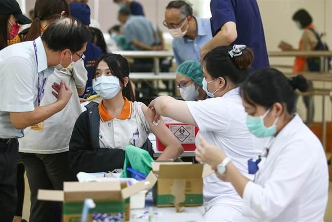 年滿12歲至未滿18歲的青少年,近日著手進行疫苗接種。圖為24日學生接種示意圖,非當事人。(鄧博仁攝)