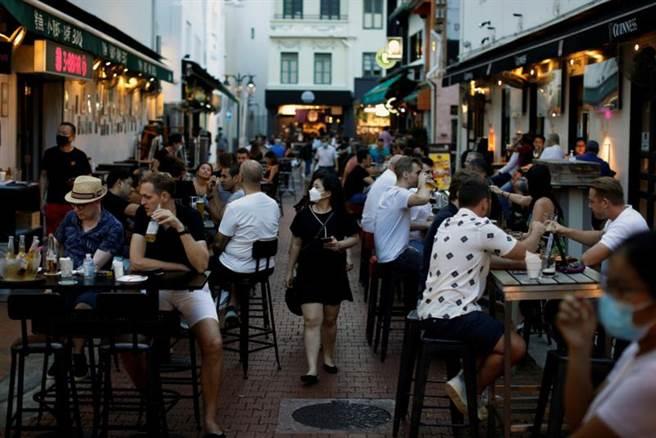 新加坡將於27日起加強防疫,包括限縮社交聚會最多2人、餐廳內用最多2人一組等。(圖/路透社)