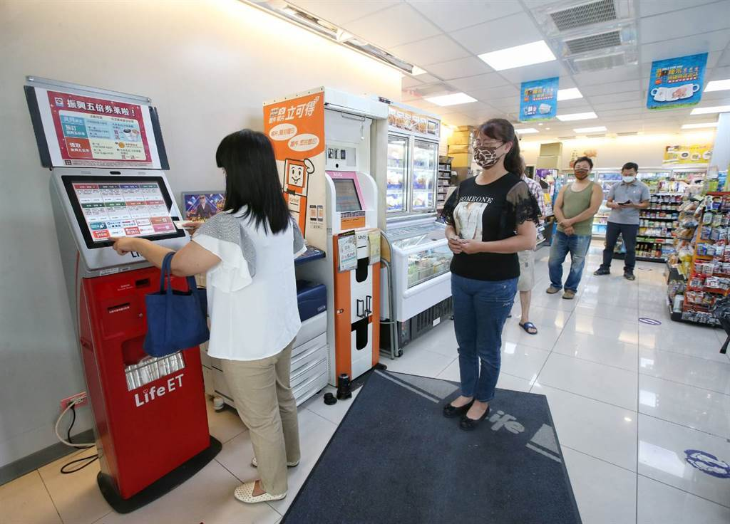 紙本五倍券今(25日)上午9時開始接受預約,超商出現人潮在事務機進行預約。(趙雙傑攝)